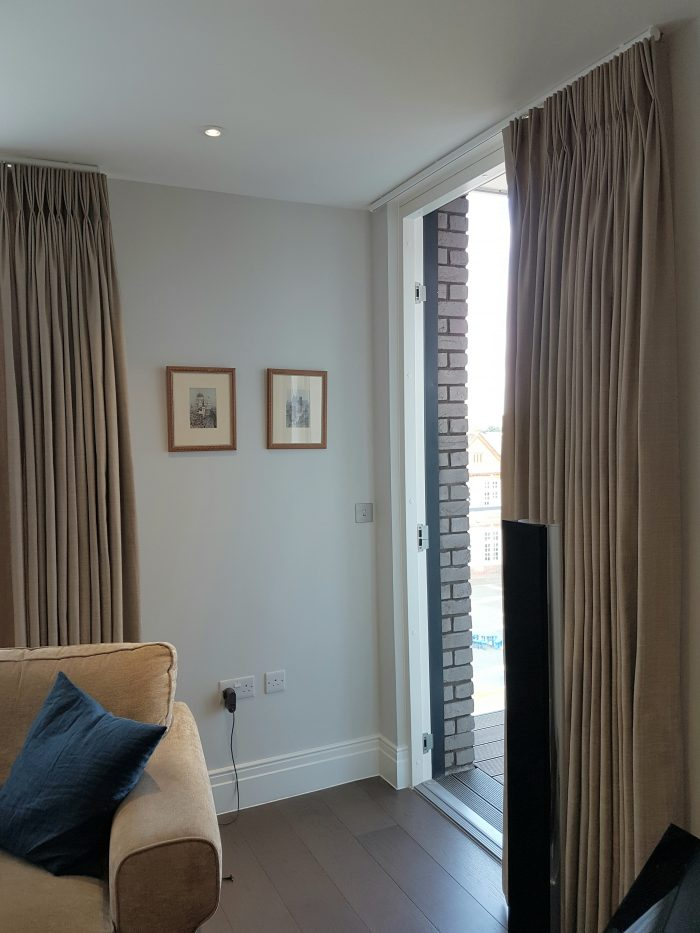 A single stack lined curtain from ceiling to floor on pole fitting to the ceiling