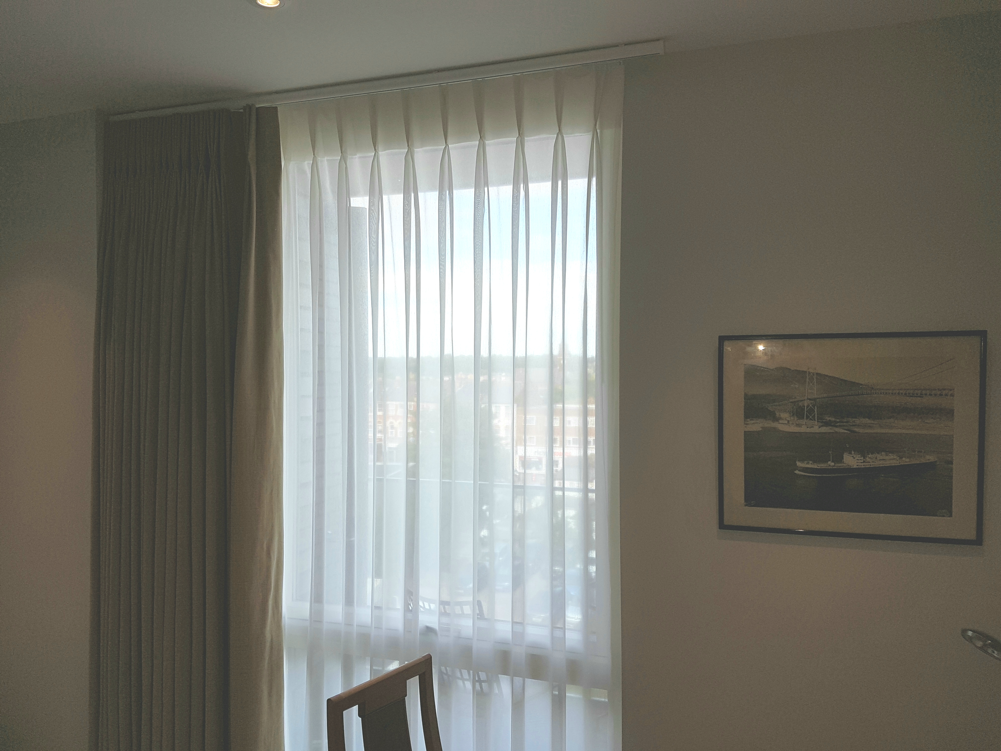 Single double pleat sheer curtain and blackout curtain installed to a curtain track and a pole