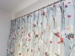 Close up of bespoke curtains and blinds in Romo botanical flower print on blue grey background