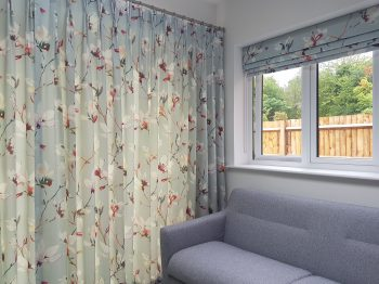 Waterfall roman blind stacked position next to curtain pole stainless steel with double pleat curtains